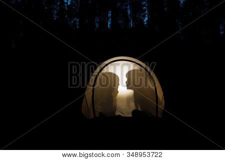 Silhouettes of children telling bedtime stories in tent at night during summer holidays camping in a forest