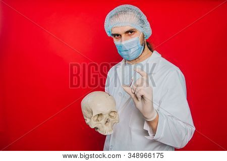 The Doctor Holds A Skull And An Ampoule With A Vaccine In His Hands. A Young Guy In A White Coat, A