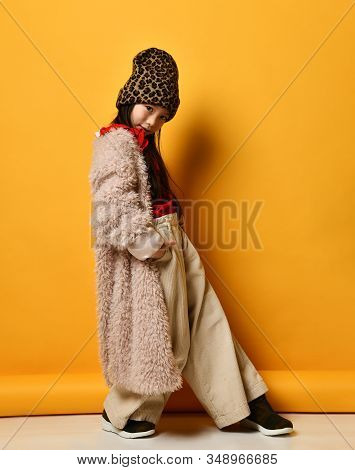 Little Asian Child In Red Blouse, Hat With Leopard Print, Beige Pants And Faux Fur Coat, Brown Boots