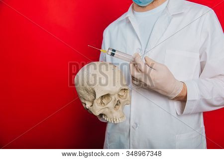 The Doctor Holds A Skull And A Syringe With A Vaccine In His Hands. A Young Guy In A White Coat, In