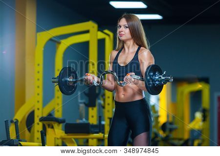 Bodybuilder Woman Lifting Curl Bar Barbell In Modern Gym. Front View. Muscles Woman Showing Sixpack