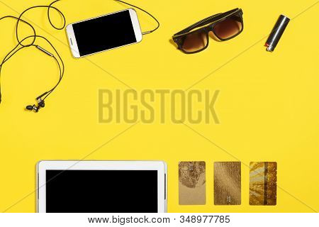 Tablet Pc, Smartphone Earphones, Cigarette Lighter, Sunglasses And Three Gold Bank Card Lying On A Y