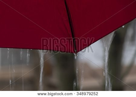Rainy Weather View From Under The Umbrella Red Umbrella Dripping Raindrops Texture Background.