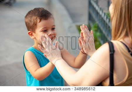 happy boy playing wallets with grandmother in the park