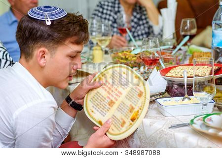Jewish Family Celebrate Passover Seder Reading The Haggadah. Young Jewish Boy With Kippah Reads The