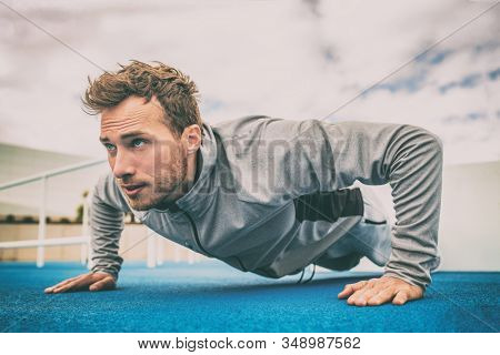 Push-up exercise fitness man training arms muscles at outdoor gym. Male athlete working out with bodyweight floor exercises.