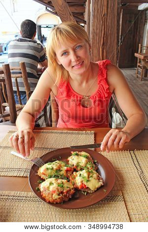 Modern Woman Dining In Restaurant. Beautiful Woman Eating Meaty Dish In Restaurant And Smiling. Woma