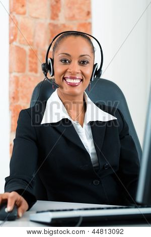 Young businesswoman or secretary working in her Office, she is sitting on the desk in front of the window and working on a computer with a headset, she has a customer pitch