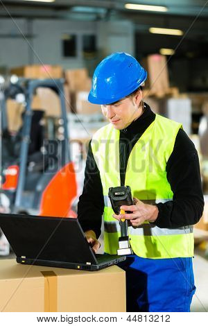 Warehouseman with protective vest, scanner and laptop in warehouse at freight forwarding company