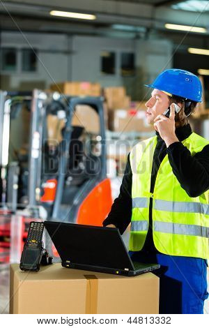 Warehouseman with protective vest, scanner and laptop in warehouse at freight forwarding company using a mobile phone poster
