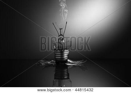Broken light bulb smoking in the dark