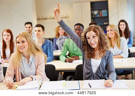 Happy student raising her hand and answering question in university class