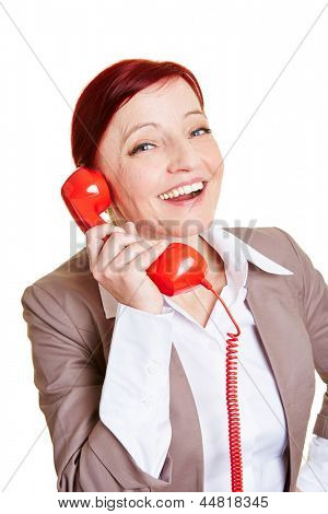 Happy best ager business woman on a red phone receiver