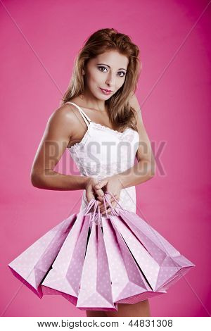 Beautiful and sexy young woman in lingerie, holding shopping bags, over a pink background