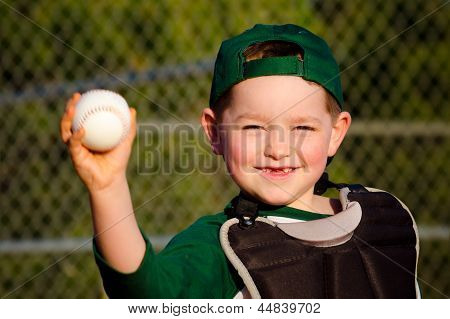 Young child in catcher's gear throwing baseball