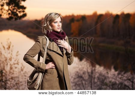 Young blond woman against an autumn nature background