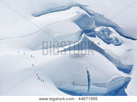 Team of alpinists traversing a dangerous glacier