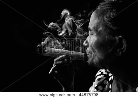 Old wrinkled Asian woman smoking traditional tobacco in monotone, black and white portrait. Bagan, Myanmar.