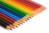 color pencils aligned in a rainbow pattern on a white background poster