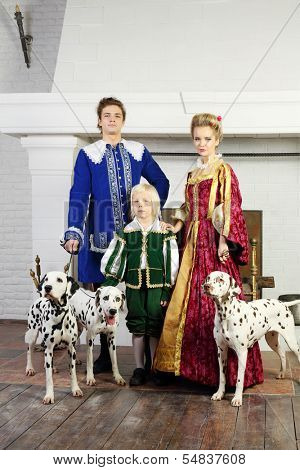 Father, mother and son in bright medieval costume pose near fireplace with three dalmatians.