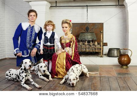 Young father, mother and little son in medieval costume stand near fireplace with three dalmatians on leashes.