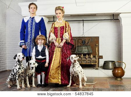 Father, mother and happy little son in medieval costume stand near fireplace with three dalmatians on leashes.