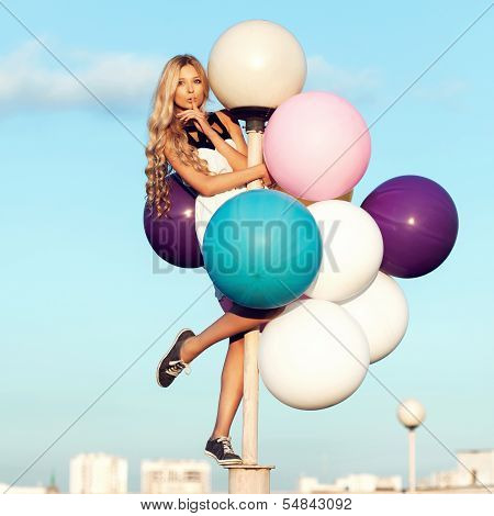 Happy young girl with big colorful latex balloons. Beauty Romantic Girl Outdoors. Woman send air kiss on lamppost on background of blue sky. poster