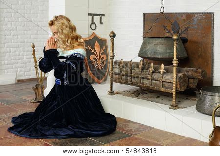 Young woman in medieval costume prays near fireplace with boiler.