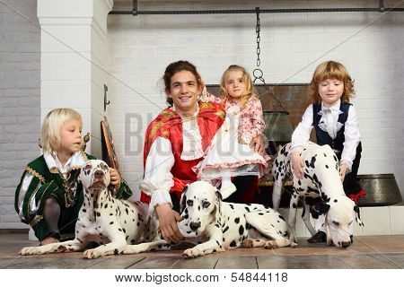 Happy father in medieval costume with three children and three dalmatians sit near chimney. poster