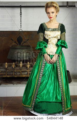 Beautiful young woman in green medieval costume stands near chimney with boiler.