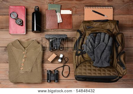 Overhead view of gear laid out for a backpacking trip on a rustic wood floor. Items include, Backpack, gloves, sweater, camera, film, binoculars, passport, wallet, canteen, compass, money,