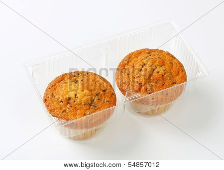 two muffins with chocolate chips in a plastic tray