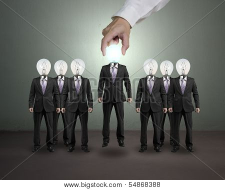 Hand Grab And Lift One Businessman With Lighting Bulb Head