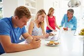 Teenage Family Having Breakfast In Kitchen With Laptop poster