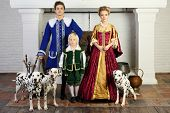 Father, mother and son in medieval costumes stand near fireplace with three dalmatians.  poster