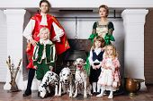 Father, mother in medieval costumes with three children and three dalmatians pose near chimney. poster