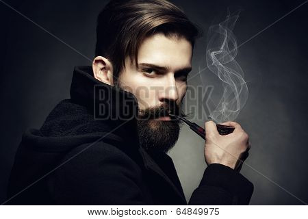 Artistic Dark Portrait Of The Young Beautiful Man. The Young Man Smokes A Tube