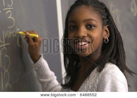 Estudante fazendo contas no quadro de giz