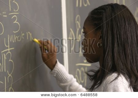 Student Writing Math Problem On Chalkborad
