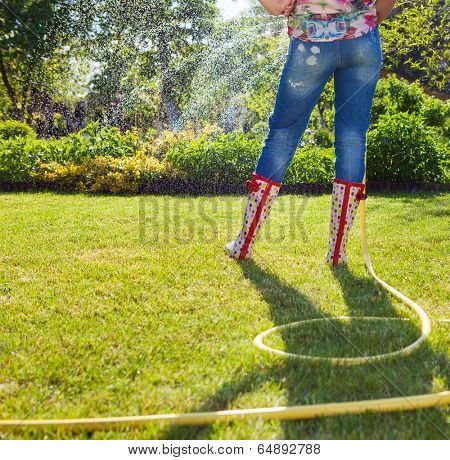 Woman holding garden water hose wearing colorful wellies watering garden