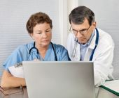 Doctor And Nurse Talking and Working at Laptop Computer In Office poster