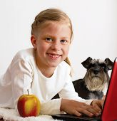 Schoolgirl studies at home on a laptop next to her is her dog poster
