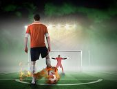 Composite image of football player about to take a penalty against football pitch under spotlights poster