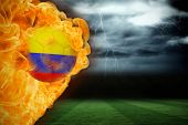 Composite image of fire surrounding colombia flag football against football pitch under stormy sky poster