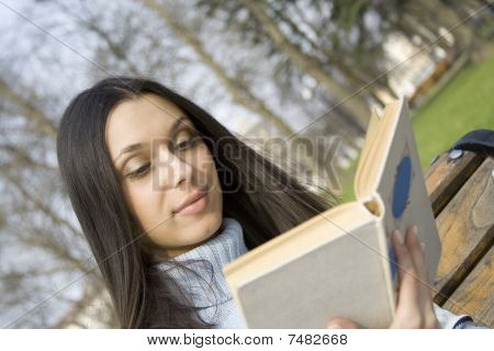 Young woman in a park reading