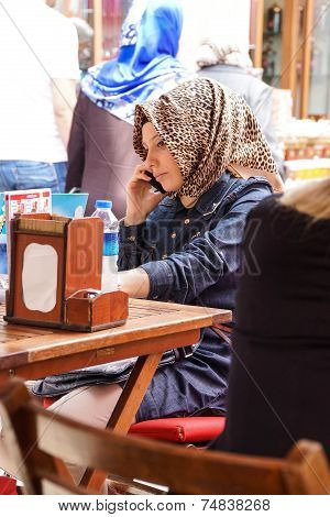 Young Turkish Woman With A Scarf Uses Her Cell Phone