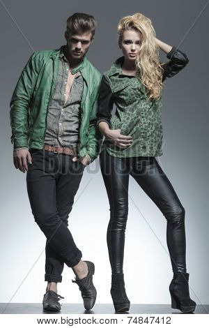 Full body image of a fashion couple posing for the camera, the woman is fixing her hair while the man is holding one hand in pocket.