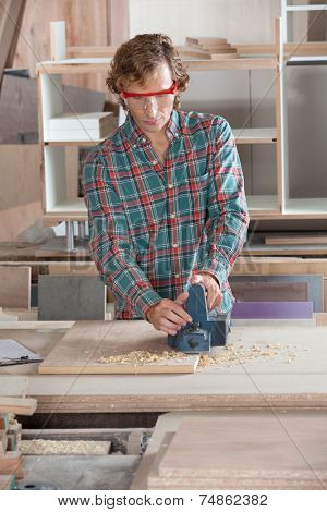 Mid adult carpenter using electric planer on wood at workshop poster