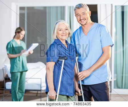 Portrait of happy male caretaker and disabled senior woman with female nurse in background at nursing home yard