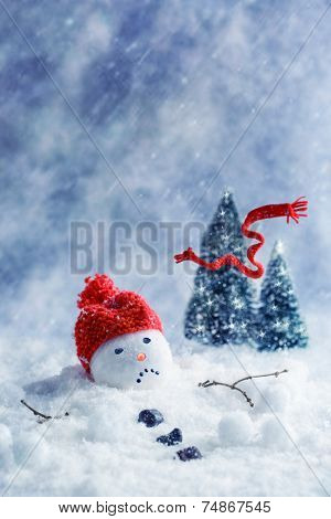 Snowman melting with scarf blowing away into Christmas trees